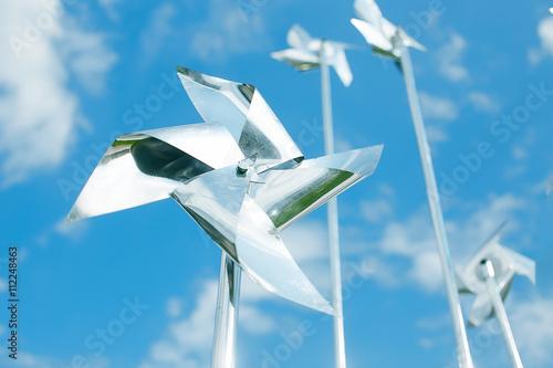 Fotografia, Obraz  metal pinwheels on background blue sky