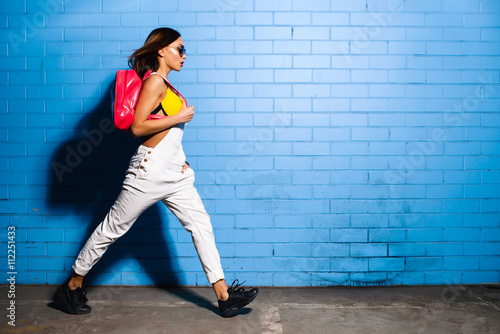 Fotografie, Obraz  Beautiful young sexy hipster girl goes near urban blue wall background in yellow swimsuit, white jumpsuit, sneakers, sunglasses, pink backpack