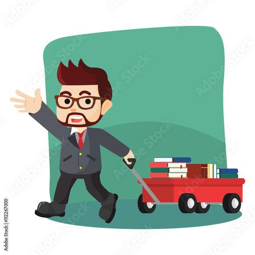 Fotografía  boy pulling a cart full of book