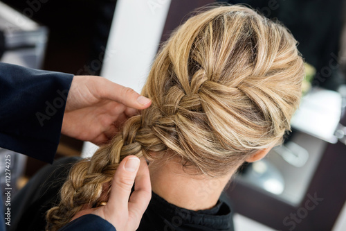 fototapeta na drzwi i meble Closeup Of Hairstylist's Hands Braiding Client's Hair