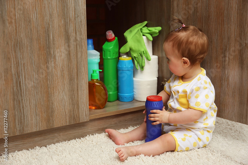 Photo Little girl playing with detergents in kitchen