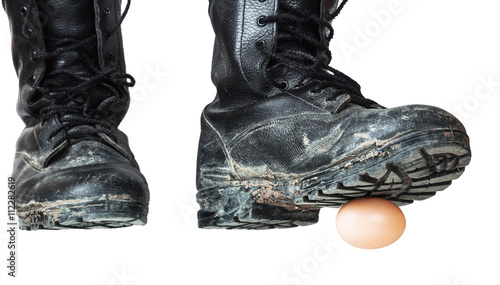 38000728b02 Old black army boots trampling egg. The egg as a symbol of the ...