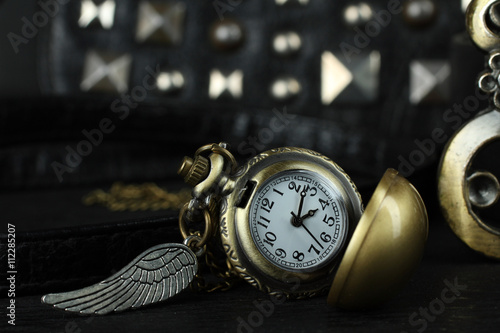 Fotografie, Obraz  women's bag with old clocks as a pendant on a black background