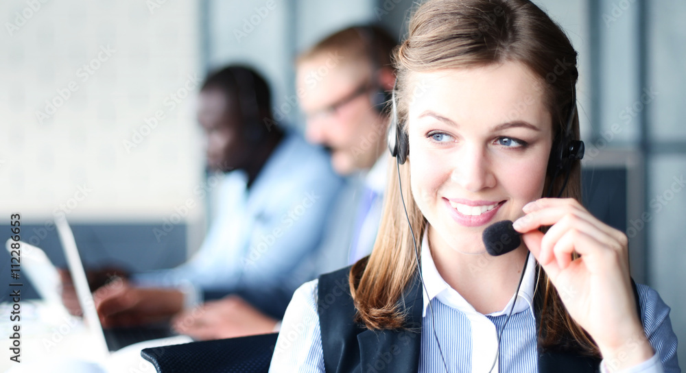 Fototapeta Portrait of call center worker accompanied by her team. Smiling customer support operator at work.