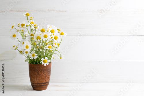 Staande foto Lelietje van dalen Daisy flowers bouquet in clay vase on white wooden shabby board.