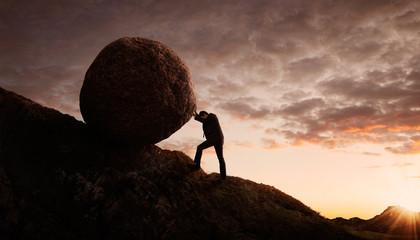 Young businessman pushing large stone uphill