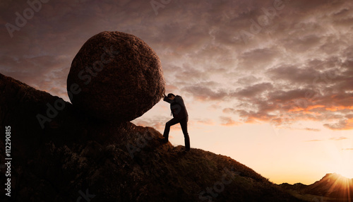 Fotografie, Obraz  Young businessman pushing large stone uphill