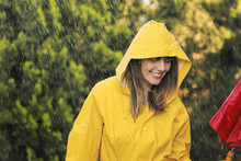 Woman In Raincoat With Umbrella Out In The Rain