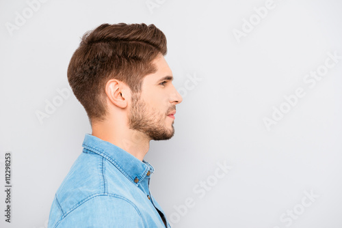 Valokuva  Side view of young bearded man isolated on gray background