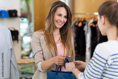 Woman Paying With Credit Card In Clothing Store Kaufen Sie Dieses