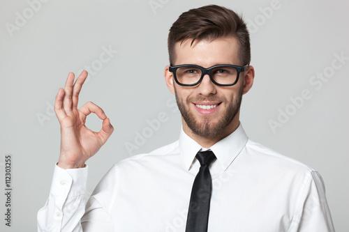 Valokuva  Handsome businessman showing okay sign on gray background.