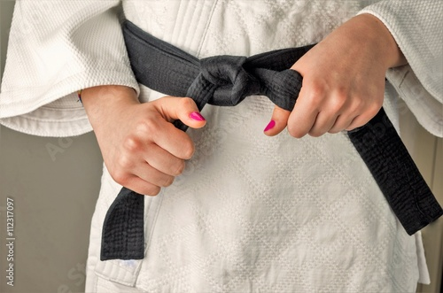 Deurstickers Vechtsport Hands with nail polish of a girl with a black belt in martial arts, close up