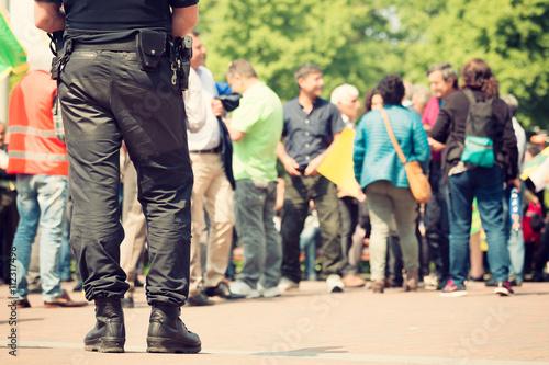 Fototapeta Ozbrojený policista stojí stráž na protest Mars ve městě,