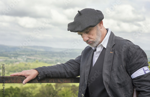 Poster  Portrait image of a French Resistance soldier looking down to the floor, with green fields in the background