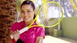 Calm beautiful young athletic woman in pink blouse holding yellow tennis racket over shoulder under the shade near palm tree