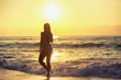 Silhouette of carefree woman on the beach
