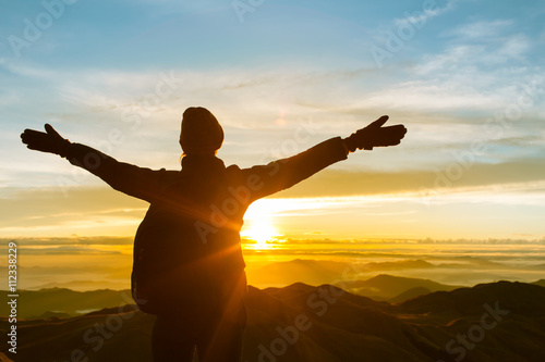 Fotografia  Happy celebrating winning success woman at sunset or sunrise standing elated with arms raised up above her head in celebration of having reached mountain top summit goal during hiking travel trek