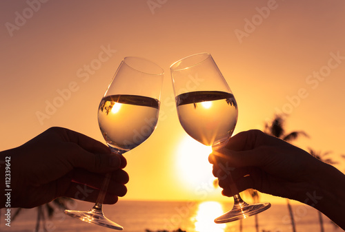 Fotografía  Cheers to a beautiful life! Pair of wine glasses toasting against a beautiful sunset