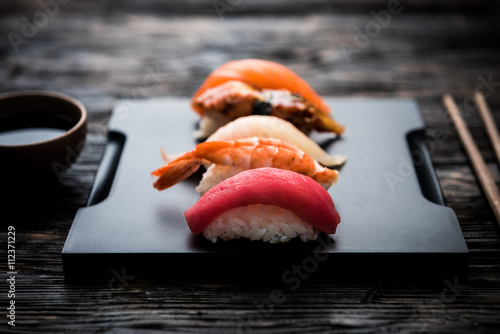 Poster Sushi bar sashimi sushi set with soy on black background