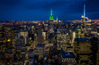 Aerial view of midtown Manhattan at night, the heart of a financial empire that dominates the business world, with every building vividly colored in shades of blue and green in NYC