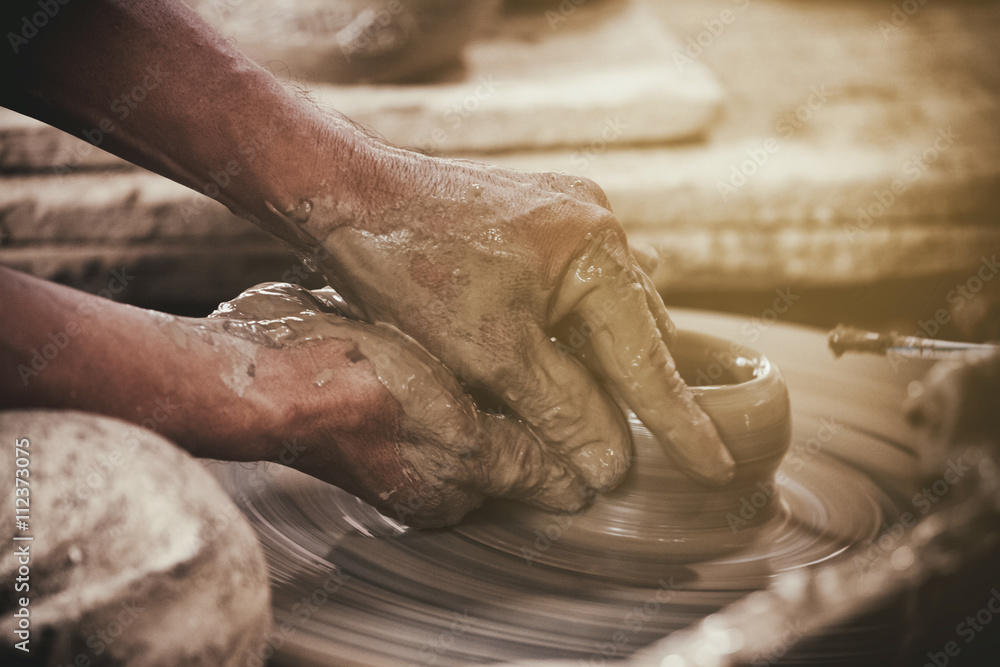 Fototapety, obrazy: Potter makes on the pottery wheel clay pot.
