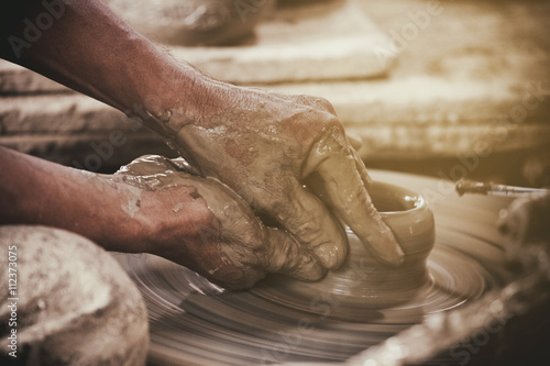 Stampa su Tela Potter makes on the pottery wheel clay pot.