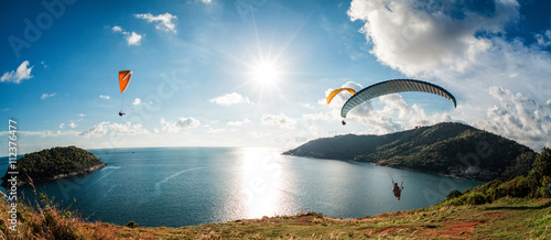 Fotografie, Obraz  Paraglider flying over the water