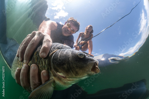 Fisherman holds a fish in water