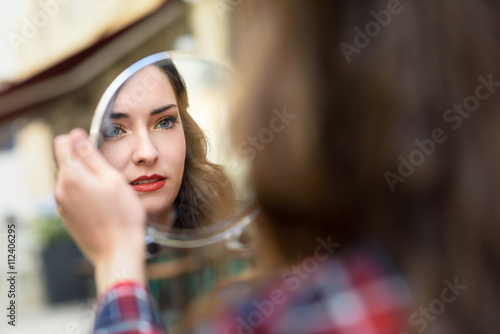 Fotografía  Young woman looking at herself in a little mirror