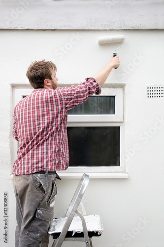 Man painting house wall on stepladder with paint roller  DIY