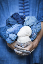 A Man Holding Balls Of Wool Dyed With Natural Indigo Color