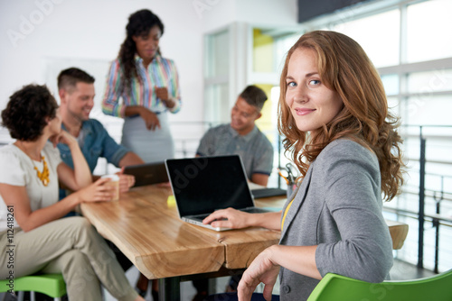 Image of a succesful casual business woman using laptop during meeting Wallpaper Mural
