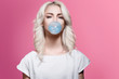 canvas print picture - Beautiful blonde girl inflates a bubble of gum blue on a pink background