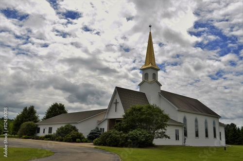 Church building with steeple and belfry against a partly cloudy summer sky