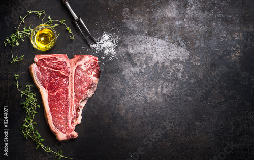 Keuken foto achterwand Steakhouse Raw T-bone Steak with fresh herbs and oil on dark rust metal background, top view, place for text, horizontal