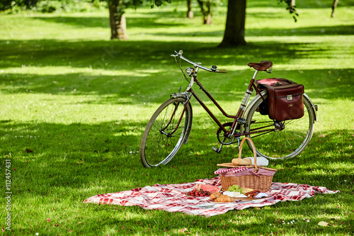 Photo sur Toile Pique-nique Bicycle and picnic spread in a lush green park