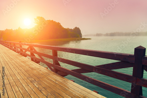 fototapeta na lodówkę Wooden bridge over lake in early misty morning
