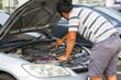 man repairing a car with a raised soot