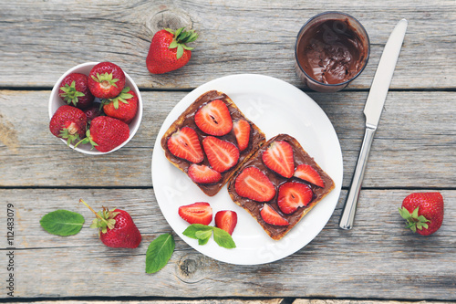 French toasts with chocolate and strawberry on wooden table Canvas Print