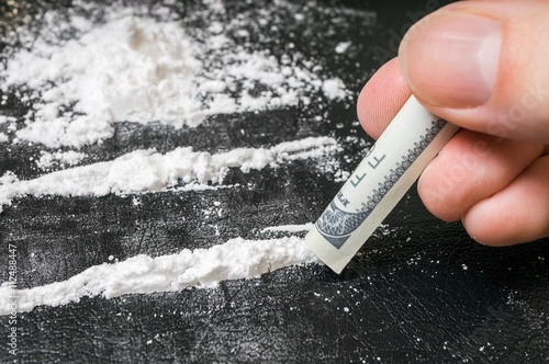 Photo  Hand of man holds rolled banknote for snorting cocaine powder.