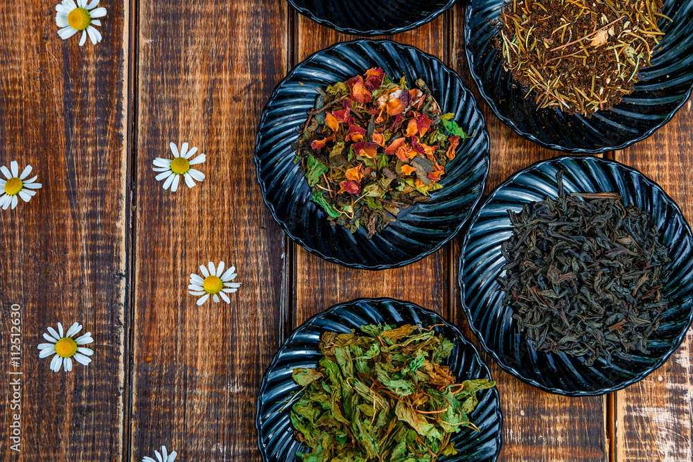 Different kinds of tea on plates on wooden background with flowers of chamomile . Assortment of dry tea. Tea concept. Tea leaves. Top view. Copy space, frame.