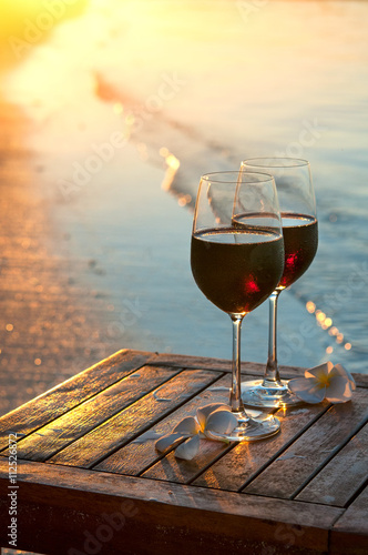 Canvas Prints Vineyard Romantic beach scene: two glasses of red wine at sunset near water