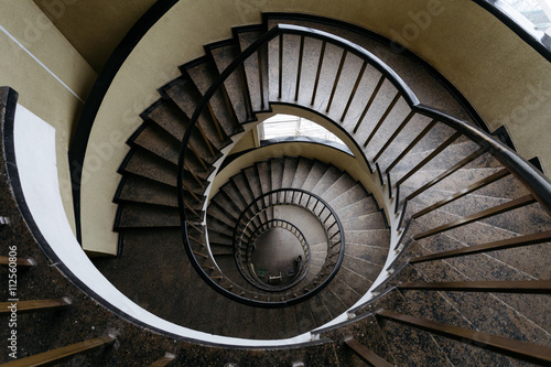 Fototapety, obrazy: Spun circular staircase with a handrail in a building without people.