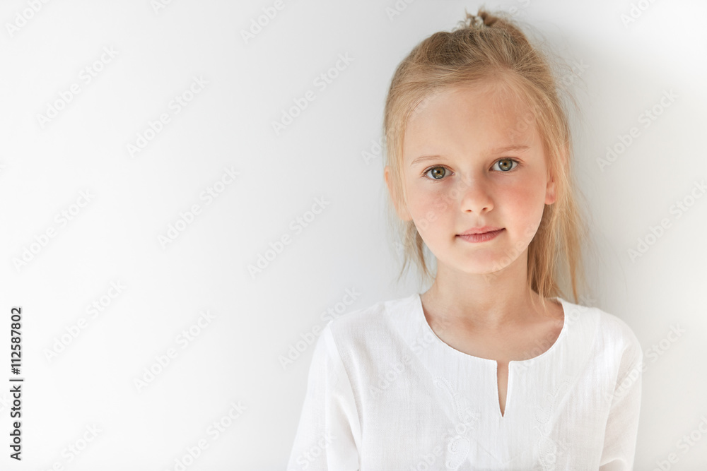 Fototapeta Blond Caucasian female child with green eyes standing quietly indoors and looking straight forward in good and sunny day. White colors make little girl look like a little angel or innocent baby.