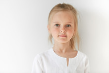 Little European Girl In White Children Clothes Looking Peacefully At The Camera Indoors. Calm Child Standing Quietly In Restful Manner With Angelic Look And Innocent Appearance.