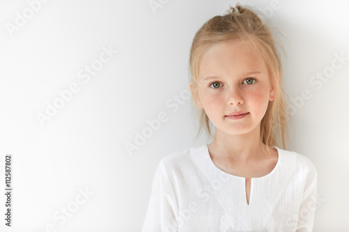 Obraz Blond Caucasian female child with green eyes standing quietly indoors and looking straight forward in good and sunny day. White colors make little girl look like a little angel or innocent baby. - fototapety do salonu