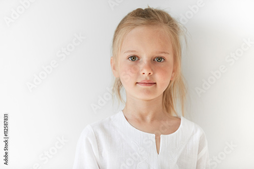 Little European girl in white children clothes looking peacefully at the camera indoors Fototapet
