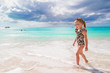 Adorable little girl have fun at shallow water on white beach