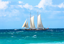 Vintage Tall Sail Boat With Masks High Sailing Off The Coast On The Blue Choppy Ocean Lit Up By Sunshine.