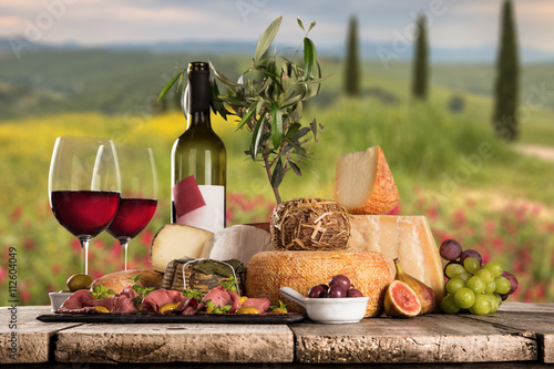 Foto  Delicious cheeses with wine on old wooden table.